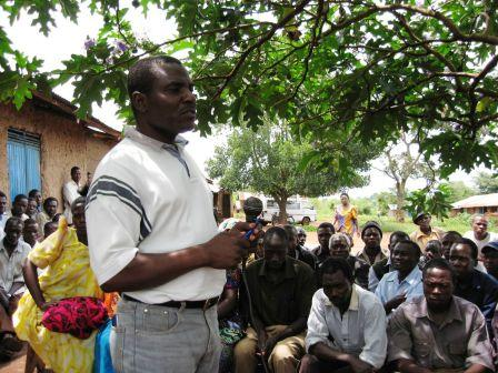 Odembo_speaking_with_villagers_under_a_t